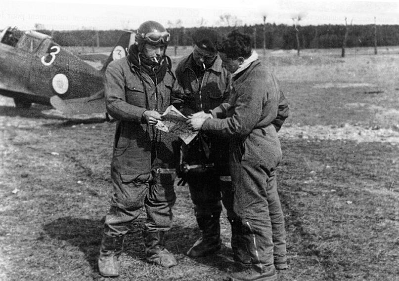 Adjudant Roger (links) van de GC III/3 neemt op vliegveld Toul-Ochey met Sergent Bret en Sous-lieutenant Sauvage een missie door, voorjaar 1940. Roger claimt op 13 mei twee Bf109's bij Breda. In de Morgen met tactisch nummer '3' op de achtergrond sneuvelt Capitaine Trouilland bij Etten-Leur (B. Hugot).